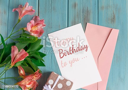 Happy Birthday to You. Birthday greeting card with flowers on a wooden background. Greeting card for girls, congratulations on mother's day.