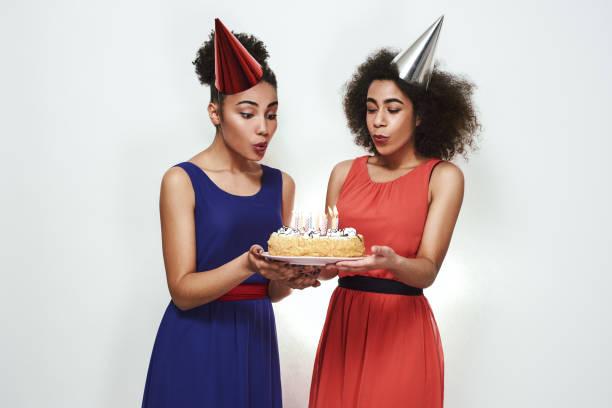 herzlichen glückwunsch zum geburtstag! zwei attraktive und junge afro-amerikanische frauen in partyhüten und abendkleidern blasen auf einer geburtstagstorte die kerzen aus - marinekuchen stock-fotos und bilder