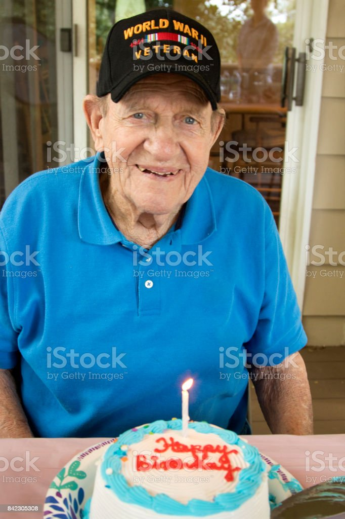 Happy Birthday World War Two Veteran with cap, sitting with Birthday Cake with lit candle stock photo