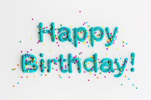 Blue buttercream frosting spelling happy birthday!