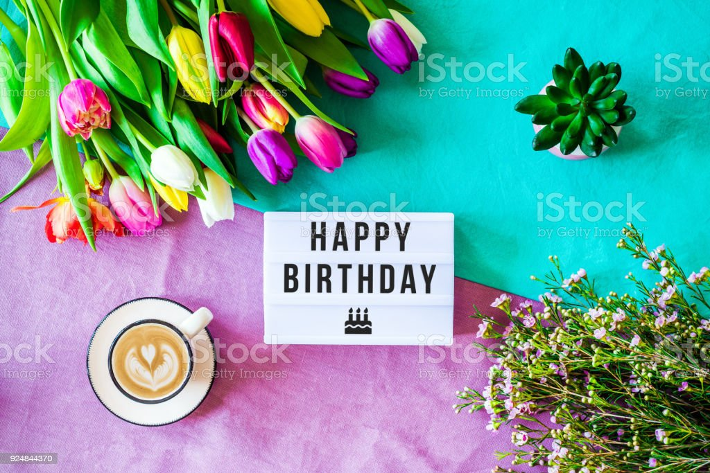 Happy Birthday Written In Lightbox With Spring Flowers From Above