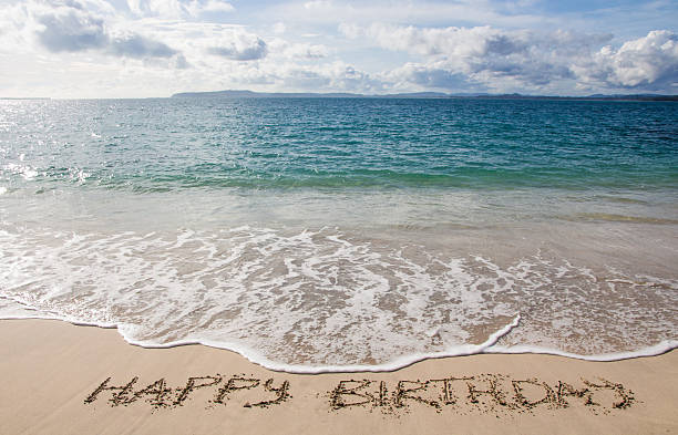 Happy birthday written in the sand on the beach stock photo