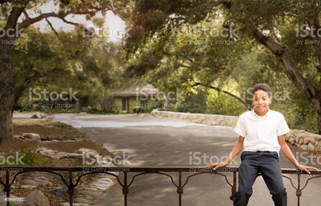 Happy Black African American boy sitting on iron gate stock photo