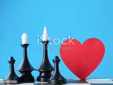 istock happy black afro-american family concept. chessman king, queen and two pawns near red heart with blue background 1129677224