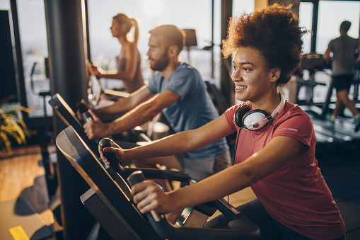 istock Happy black athlete practicing on exercise bike in a health club. 909443742