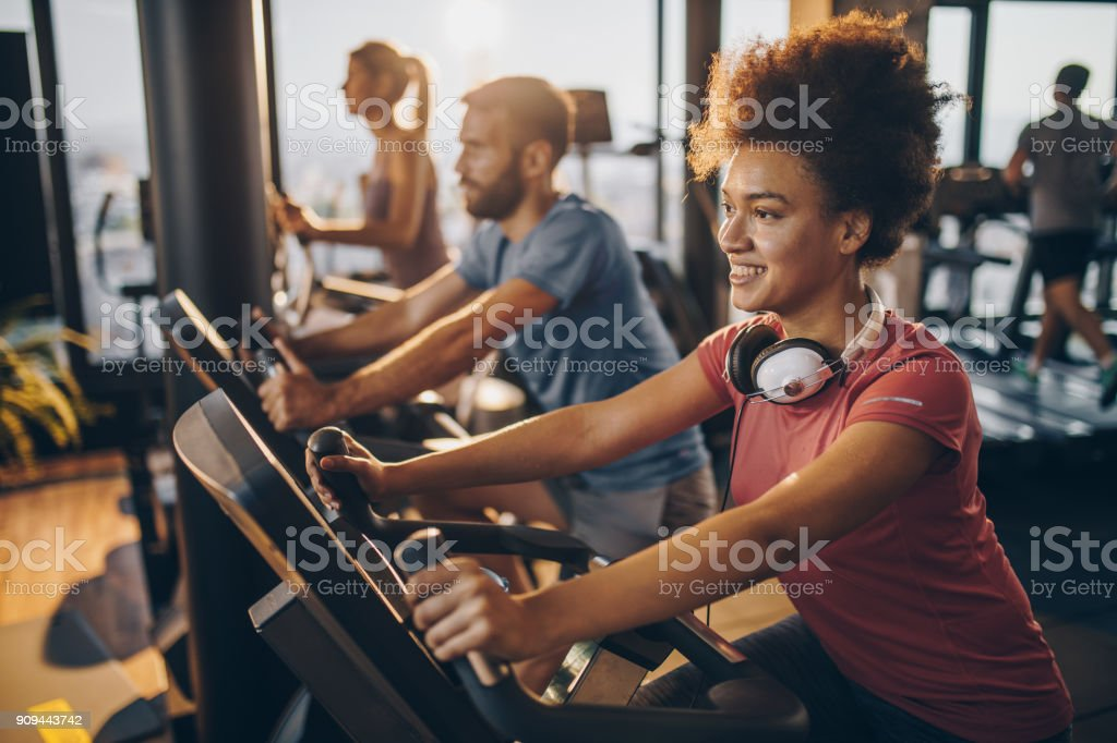 Happy black athlete practicing on exercise bike in a health club. stock photo