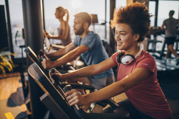 happy black athlete practicing on exercise bike in a health club. - health club stock photos and pictures