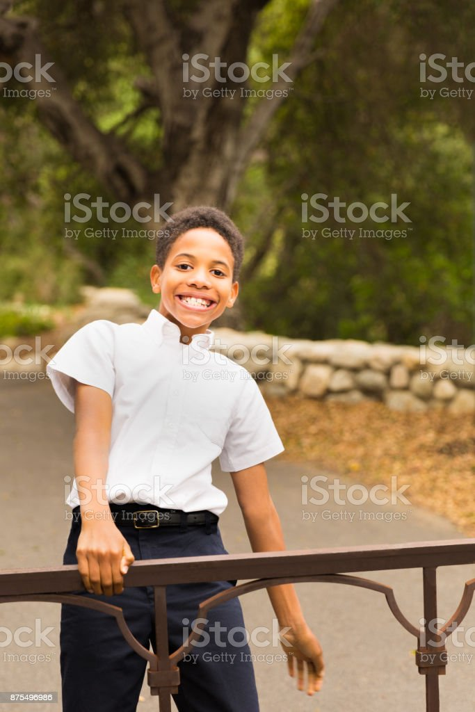 Happy Black Boy Playing on Gate stock photo