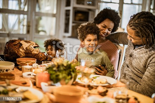 Happy black boy communicating with his parents while having Thanksgiving meal in dining room.