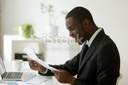 istock Happy black businessman reading mail letter with good positive news 916520020