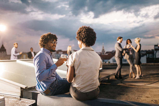 Happy black businessman toasting with his colleague on a rooftop party. stock photo