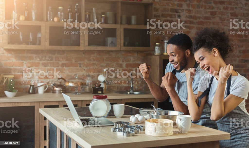 Happy black couple cooking pastry looking on laptop stock photo