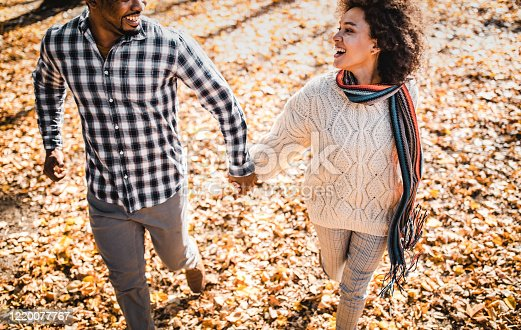 Happy African American couple having fun while holding hands and running in autumn day at the park.