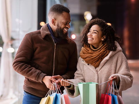 Enjoying Purchases. Portrait of happy smiling black couple holding colorful shopping bags, excited about their new clothes or gift, standing outdoors near mall in the evening, looking at each other