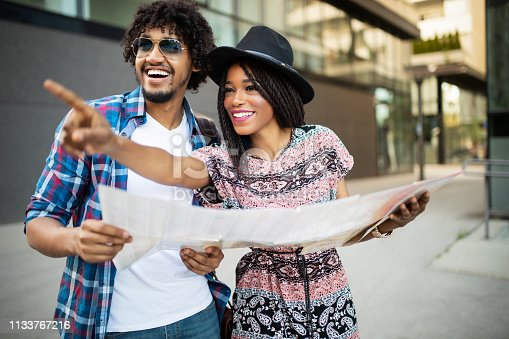 Happy african american couple on vacation sightseeing city with map