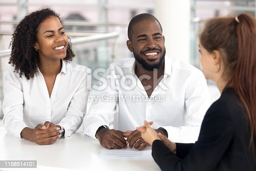 963814372istockphoto Happy black couple talk consulting with realtor in office 1158514101