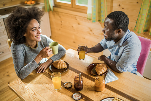Happy Black Couple Talking To Each Other During Breakfast Time At ...