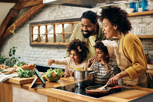 Happy African American parents and their kids having fun while cooking and following recipe on the internet.