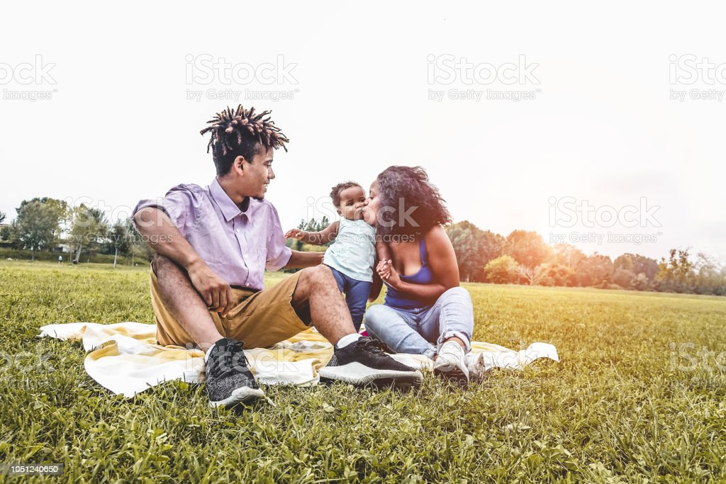 Happy black family having fun doing picnic outdoor - Parents and...