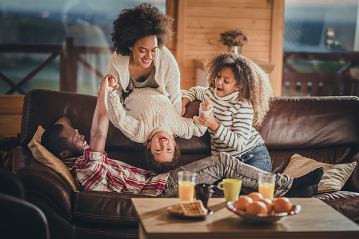 Happy Black Family Having Fun While Playing On Sofa In The