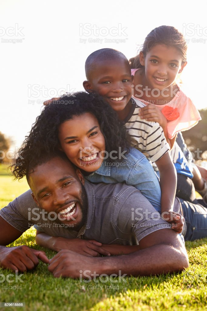 Happy black family lying in a pile on grass outdoors stock photo
