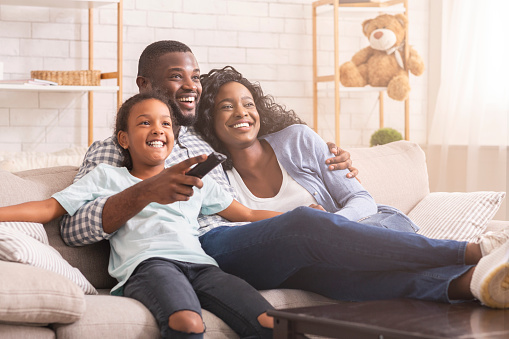 Happy african american family relaxing and watching tv at home, enjoying weekend together.