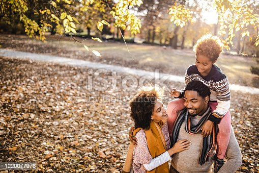 Happy African American family enjoying in autumn day at the park. Little girl is on her father's shoulders. Copy space.