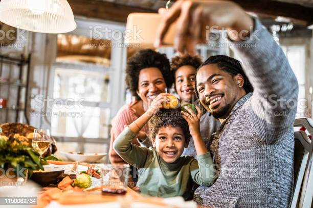 Happy black family taking a selfie with cell phone in dining room picture id1150062734?b=1&k=6&m=1150062734&s=612x612&h=rynqan3nsvpesvyxzf7h0i4uaahcogv rbbjb5 afdu=
