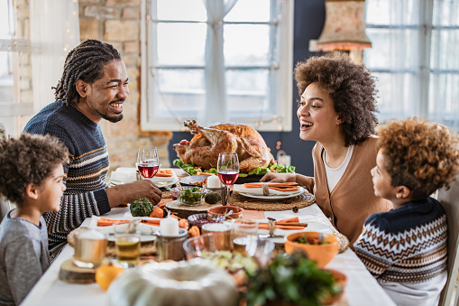 Happy African American family communicating while having Thanksgiving lunch in dining room.