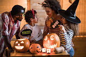 Happy African American family talking on Halloween at home.