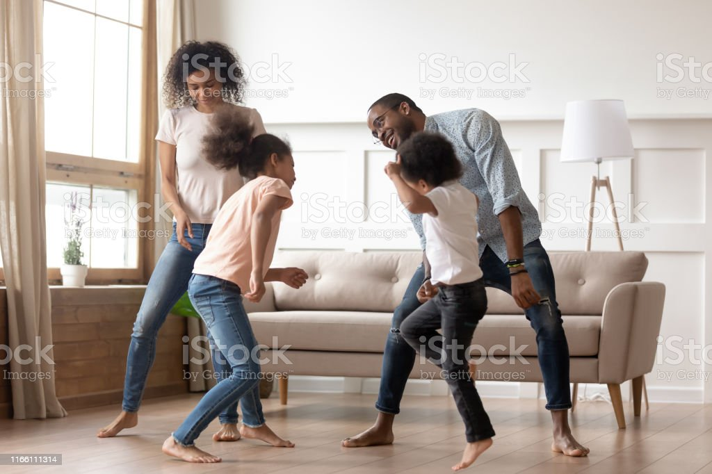 Happy Black Family With Kids Dancing Together In Living ...