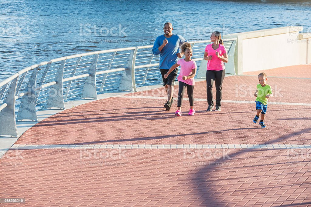 Happy black family with two small children exercising stock photo