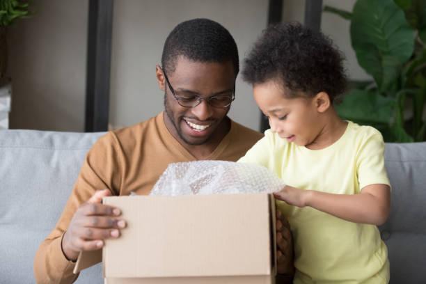 glücklicher schwarzer vater und kleiner sohn öffnen karton - kinder die schnell arbeiten stock-fotos und bilder