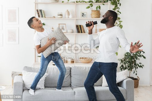 Home Entertainment. Happy african american father and little son having fun together in living room, playing and singing, boy using pillow as guitar
