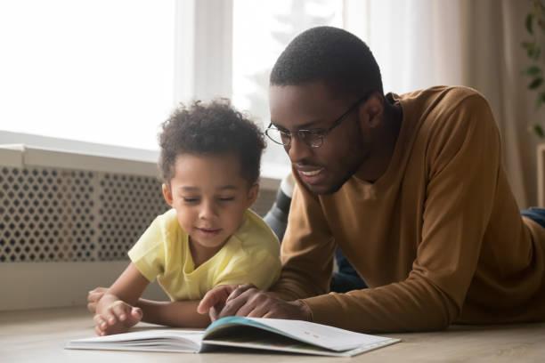 fröhlicher schwarzer vater und toddler sohn lesebuch zu hause - genderblend stock-fotos und bilder