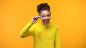 istock Happy black female looking camera through magnifying lens, shocking news, search 1142209400