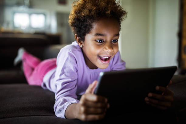 Happy black girl enjoying while watching cartoons on touchpad at home. Happy African American girl having fun while lying on sofa and using digital tablet. cartoon and kids stock pictures, royalty-free photos & images