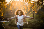 Carefree African American girl running with her arms outstretched in autumn day at the park and looking at camera.