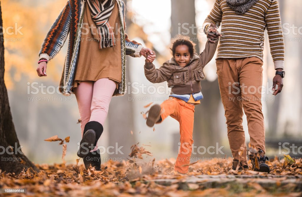 Smiling African American girl holding hands with her parents and...