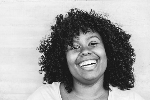 Happy black girl laughingoutdoor - Young curvy african female having fun smiling on camera - Lifestyle concept - Focus on face - Black and white editing