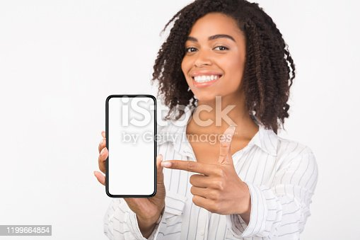 Modern Technology Concept. African american woman pointing at blank phone screen, mock up