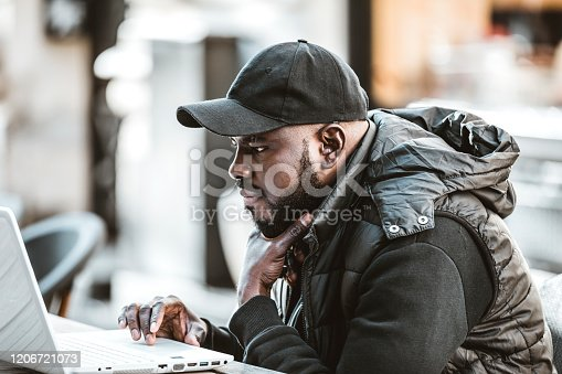 544356862 istock photo Happy black guy sitting at outdoor cafe with laptop computer 1206721073