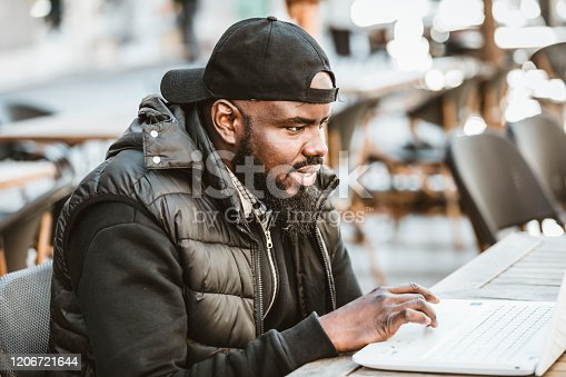 544356862 istock photo Happy black guy sitting at outdoor cafe with laptop computer 1206721644