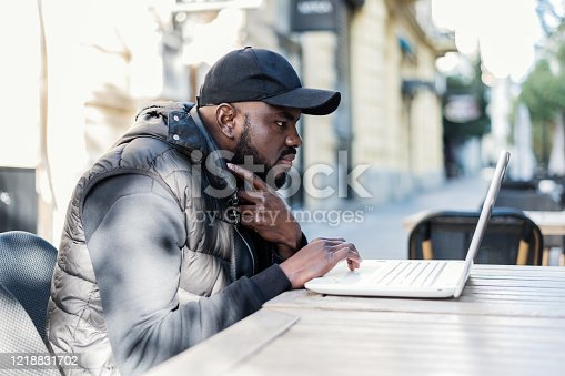 544356862 istock photo Happy black guy sitting at outdoor cafe with laptop computer 1218831702