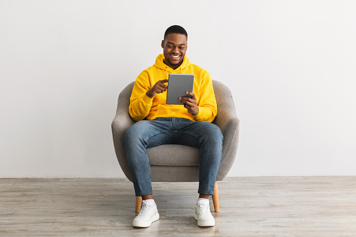 Happy Black Guy Using Digital Tablet Computer Browsing Internet Sitting In Chair Over Gray Wall Background. Online Technology And Modern Gadgets Lifestyle Concept