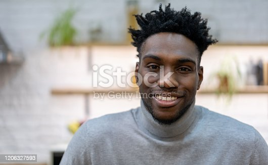 Portrait of a happy black man smiling at home and looking at the camera - lifestyle concepts