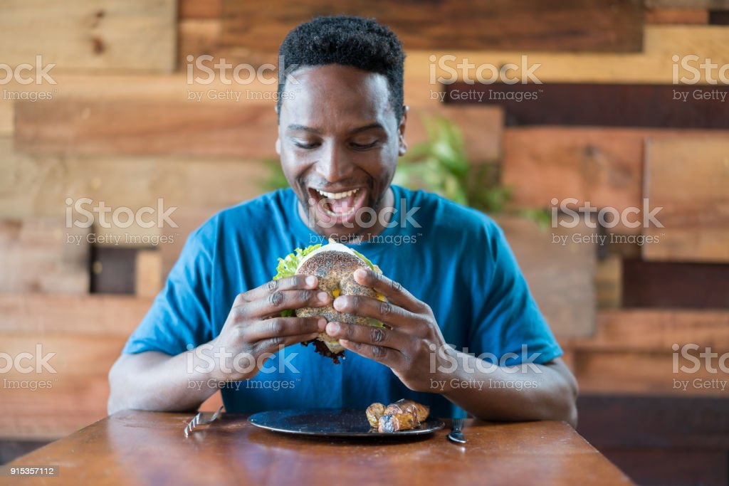 Happy black man holding a bagel with vegetables ready to eat it stock photo