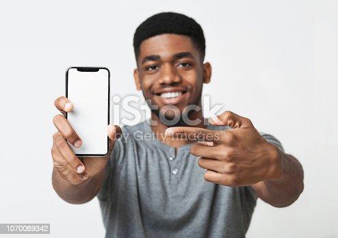 istock Happy black man holding latest slim smartphone 1070089342