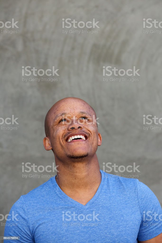 happy black man laughing and looking up stock photo