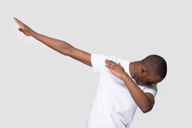 Happy black man making dab gesture on blank studio background stock photo